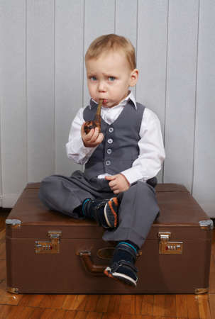 smoking pipe: photo of little funny boy with smoking pipe