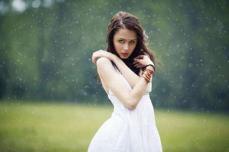sotto la pioggia: bella ragazza sotto la pioggia in estate foresta