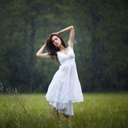 beautiful girl under rain in summer forest