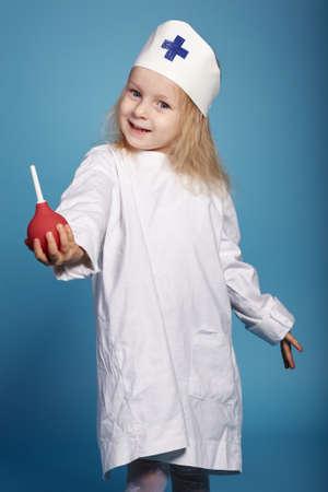 einlauf: Foto des kleinen lustigen Mädchen spielen Krankenschwester