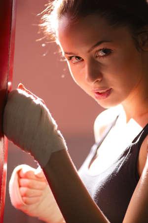 punching: beautiful girl in boxing gloves kick punching bag
