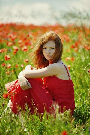 Joven pelirroja hermosa chica en campo de amapola Foto de archivo