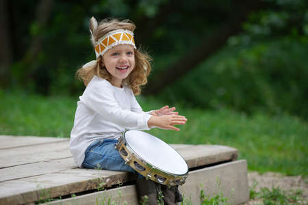 Photo of little funny girl playing native american Stock Photo