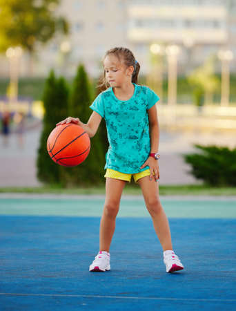 little cute girl playing basketball outdoors