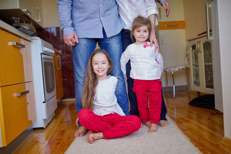 hugging legs: two little girls hugging mom and dad for legs