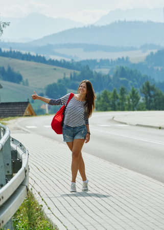 hitchhiking: Pretty young woman hitchhiking along the road Stock Photo