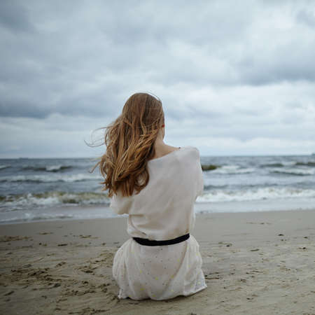 devastated: photo of young beautiful woman on cold windy beach