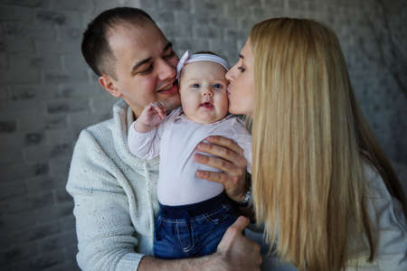 a young baby: photo of happy father and mother with baby