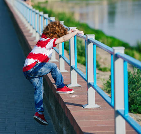 photo of little boy climbing over the fence Stock Photo