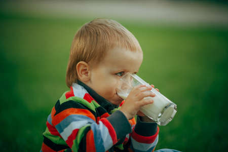 photo of little funny boy with glass of milk