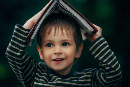 diligente: Foto de un niño con el libro en su cabeza Foto de archivo