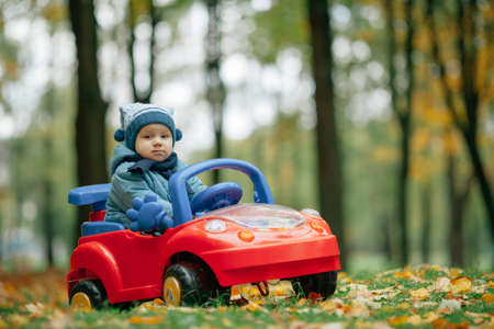game drive: photo of little funny boy driving toy car