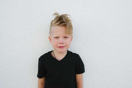 whining: photo of young emotional boy on bright background