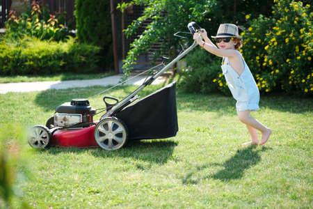 mows: little cute boy mows lawn with mower