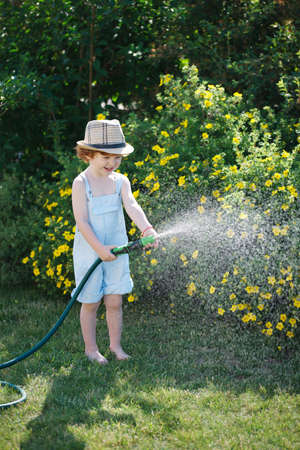 cute little boy watering the garden with hose Stock Photo