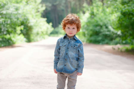 photo of cute little emotional boy outdoors Stock Photo