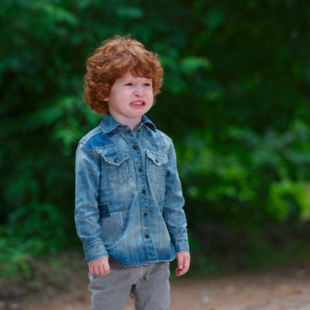 photo of cute little emotional boy outdoors Imagens