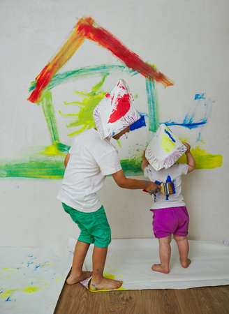 children painting: two happy children painting wall at home Stock Photo