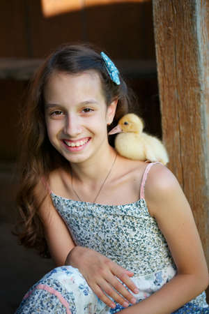 yellow duckling: young girl with little yellow duckling in summer village