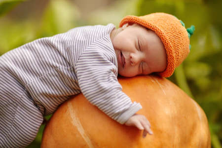 sweet baby with pumpkin hat sleeping on big orange pumpkin Archivio Fotografico