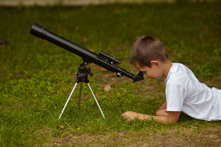 photo of happy little boy with telescope Stock Photo