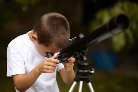 an eyepiece: photo of happy little boy with telescope Stock Photo