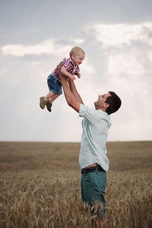 Glücklicher Vater mit Sohn auf dem Weizenfeld Standard-Bild - 62130175