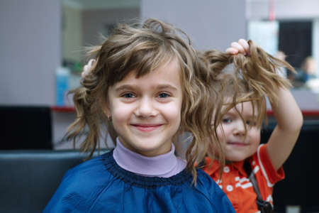 two funny children play in the barbershop