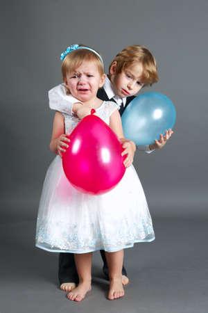 photo of little boy hugging weeping girl