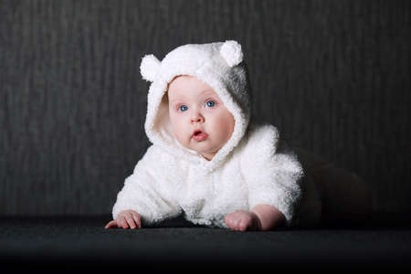 hands over ears: photo of baby in white bear costume