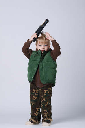 plastic soldier: photo of little boy with gun on white