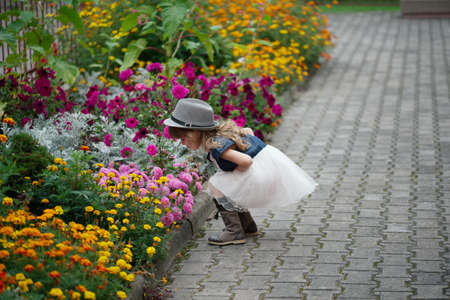 photo of little beautiful girl in flowers park Stock Photo