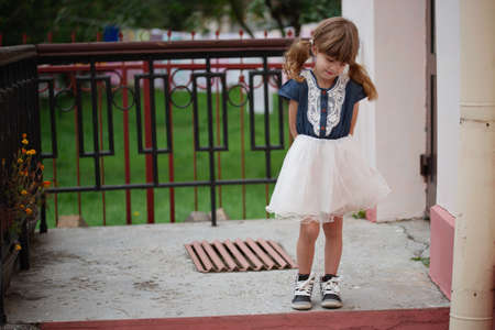 photo of little cute shy girl on the street Stock Photo