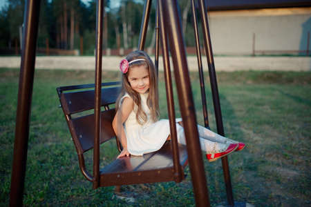 photo of young happy girl on the swings Stock Photo