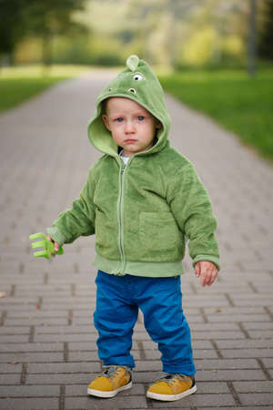 cute little unhappy boy with dinosaur costume Stock Photo