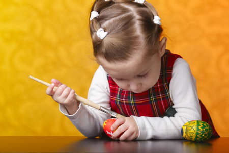 photo of little girl painting easter eggs