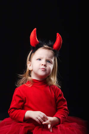 photo of funny little devil on dark background Stock Photo