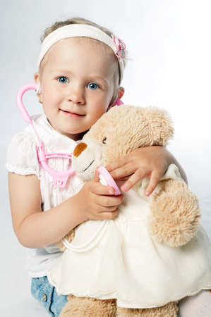 girl plays doctor with teddy bear on white