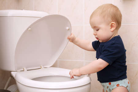 curious little boy looks in the toilet