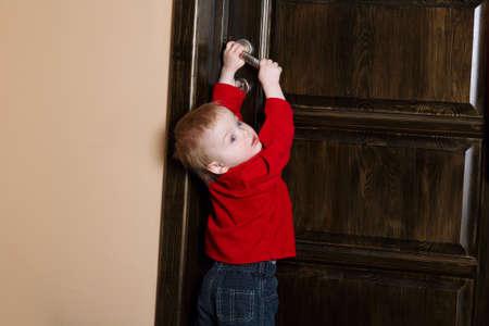 kleiner Junge versucht, Tür zu Hause zu öffnen