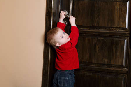 little boy tries to open door at home