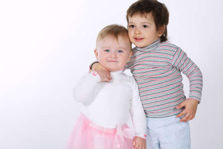two cute hugging children on white