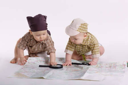 cute babies planning travel with map