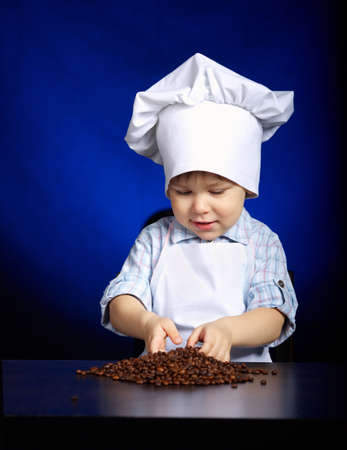 granos de cafe: little boy checking coffee grains Foto de archivo