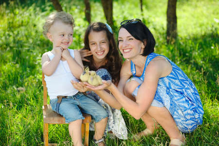 family with little yellow duckling in summer Park