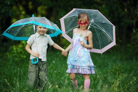 happy children under umbrella in park