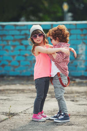 two cute hipsters hugging outdoors