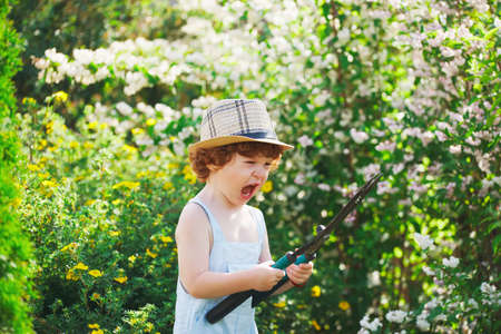 little boy watering the garden with hose Stock Photo