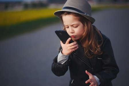 Petite fille drôle avec smartphone Banque d'images - 79342698