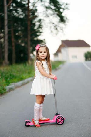 hermosa chica con scooter en la carretera Foto de archivo